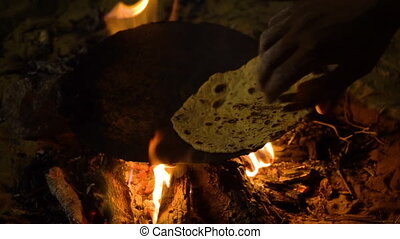 Traditionally preparing pita bread on a hot plate - A man...