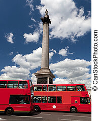 Trafalgar Square in London, the UK. Red bus in motion
