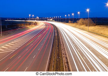 Motorway traffic driving at night just as it goes dark with traffic travelling at speed in both directions.