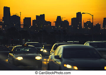 Traffic at nightfall in city with Miami Skyline on background.