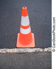 Traffic cone on newly paved driveway.