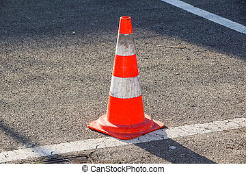 traffic cone, with white and orange stripes on gray asphalt,