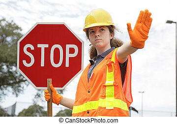 Traffic Directing Stop - A female construction worker...
