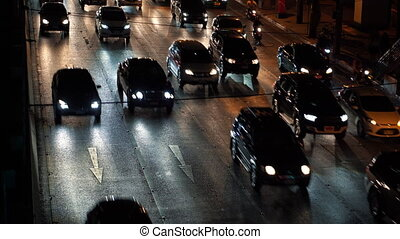 Traffic during rush hour, vehicles driving on multiple lane road at dark time