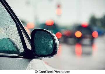 Traffic in heavy rain in the city. Raindrop on the mirror of...