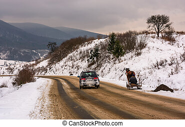 traffic in mountainous rural area in winter. cart with one...