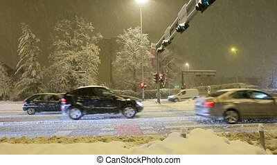 Traffic in the city, snow falls