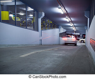 Traffic in underground parking garage. Motion blur from moving car. Number plates and trademarks erased.