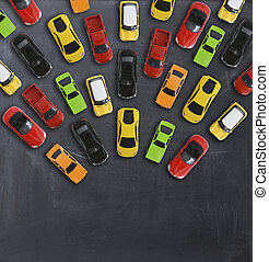 Traffic jam concept with multiple toy cars on a blackboard