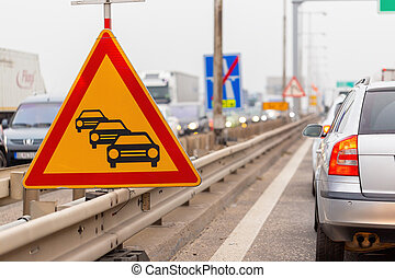 Traffic jam sign on a highway with line of cars waiting in row