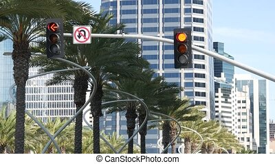 Traffic light and caution sign, road intersection in USA. Transportation safety, rules and regulations symbol. Driveway crossing attenion signal against modern urban cityscape, San Diego, California.