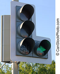 traffic light on the blue sky background. Green arrow to the right is shining.