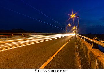 Traffic light trails at night on a bridge.