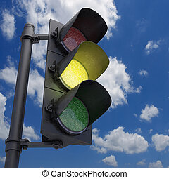 Traffic Light in a blue sky with only the yellow light on.