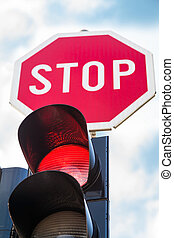 Traffic lights with the red light lit and stop sign