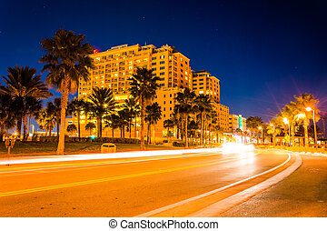 Traffic moving past a hotel and palm trees on Coronado Drive at