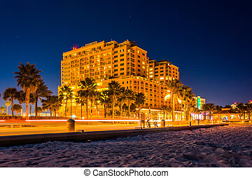 Traffic moving past a hotel and the beach at night, in Clearwate