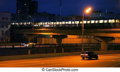 traffic of cars and light rail train in night street of Moscow, Russia
