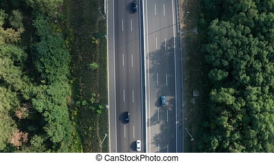 Traffic on a suburban expressway - aerial drone view. 90 degree view of the motorway autobahn with moving cars.