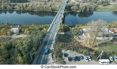 Traffic on a two-lane road bridge from a birds eye view. Top-down view of the landscape design of a suburban neighborhood. View from a flying drone to the road bridge and moving vehicles.