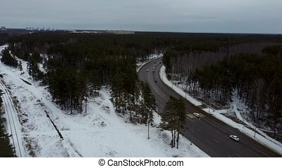Cars on road in winter with snow covered trees aerial view.