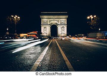 Traffic on Avenue des Champs-Élysées and the Arc de Triomphe at night in Paris, France.