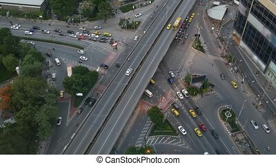 Traffic on crossroad on street. From above modern cars and motorcycles driving on intersection on street in center of Bangkok, Thailand.