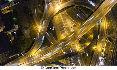 Traffic on freeway interchange. Aerial night view timelapse city traffic. UHD