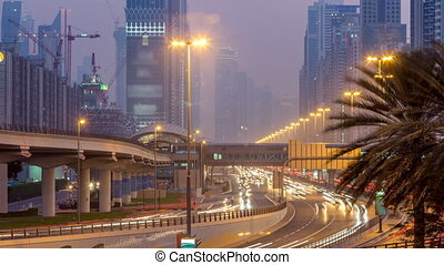 Traffic on intersection and bridge at the Sheikh Zayed Road day to night timelapse