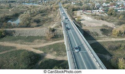 Traffic on the road from a birds eye view. Top-down view of the landscape design of a suburban neighborhood. View from a flying drone to a suburban area with car traffic and moving vehicles.