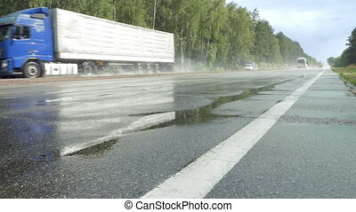 Traffic on wet road highway with mist splash