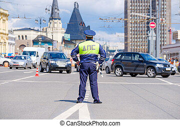 Traffic policeman works on a street at day time