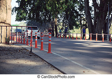 Traffic regulation pole and rumble strip on asphalt road in public park with people exercise background in the evening of sunny day. The symbol of safety first.