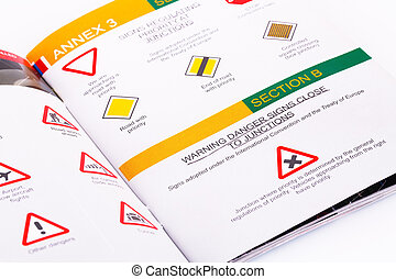 Traffic rules study book opened page with road signs.