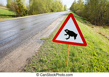 Traffic sign attents for frog migration on road