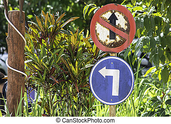 Traffic sign circle Which is prohibited to go straight and turn left Background blurry tree.