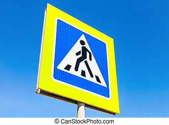 Traffic sign pedestrian crossing with blue sky in background