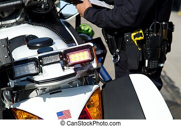 a view of a police motorcycle as the officer writes a ticket. The officer was left slightly out of focus on purpose.
