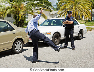 Motorist trying to walk a straight line while a police officer looks on.