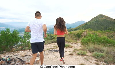 Trail runner man and woman running over mountain path. Beautiful mountainous view. Girl encourage and motivate tired boy. Jogging female and male athlete working out.