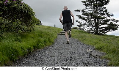 Trail Runner Passes By - A trail runner passes the camera to...
