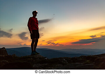 Trail runner with head lamp on top of mountain peak at...