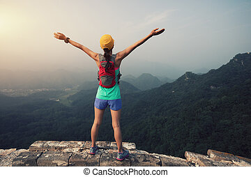 trail runner woman open arms at great wall on the top of ...