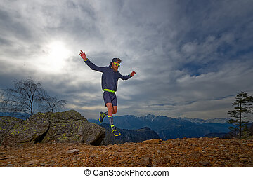 Trail running athlete jumps between the rocks