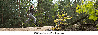 Trail running in the forest - Woman training trail running ...