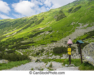 Trail signpost at footpath trail in mountain valley Smutna dolina with rock boulders, scrub pine and green mountain peaks. Western Tatras mountains, Rohace Slovakia, Summer blue sky white clouds background