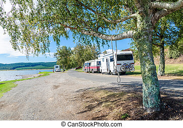 Trailer caravan in Lake Taupo,New Zealand. People can seen exploring around it.