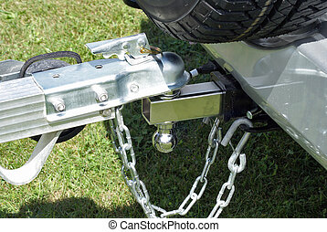 A trailer is secured to the back of a powerful vehicle to be towed to its destination for unloading.