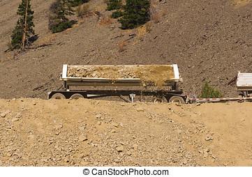 Trailor side-dumping dirt - A truck trailor side-dumping a...
