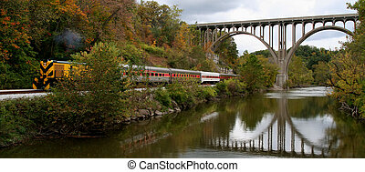 Beautiful bridge, river, and train in Autumn. Bridge is relected in the water.